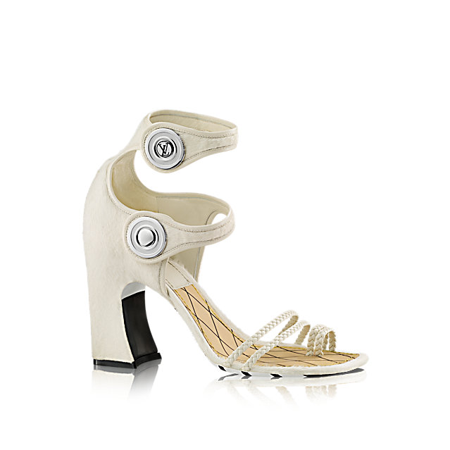 One of the statements of Louis Vuitton's 2015 Cruise collection, this striking sandal in pony-style calf leather is characterized by its double ankle strap, outsize LV-engraved snap fasteners, high, chunky heel, and black and white-striped outsole.